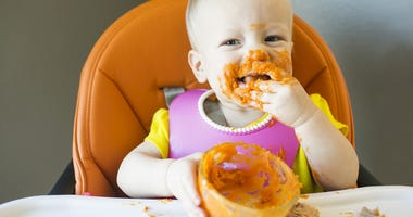 Baby sitting in high chair eating sweet potatoes with food on her face