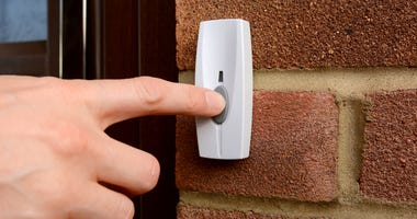 Close-up of woman pressing the button of a doorbell on a brick wall