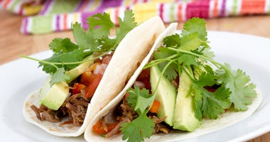 Pulled pork soft taco with avocado and cilantro