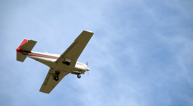 Small Plane with wheels out coming in for a landing.