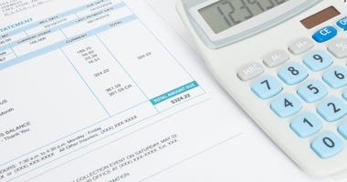 Close up shot of unpaid utility bill and calculator over it