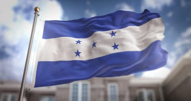 Honduras Flag 3D Rendering on Blue Sky Building Background