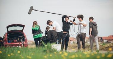 Film crew team filming movie scene on outdoor location.