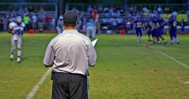 Football coach looks out at the field.