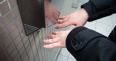 Man drys his hands in a public bathroom.