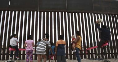 kids on seesaw at U.S. Mexico border