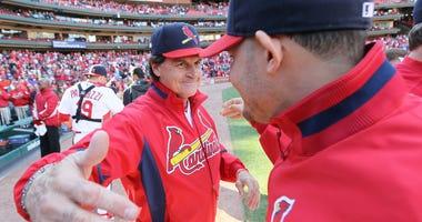 Cardinals manager Tony La Russa (left) embraces catcher Yadier Molina