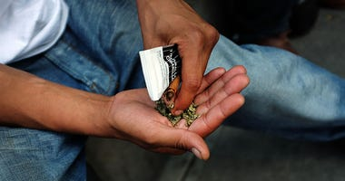 NEW YORK, NY - AUGUST 05: A man prepares to smoke K2 or 'Spice', a synthetic marijuana drug, along a street in East Harlem on August 5, 2015 in New York City.