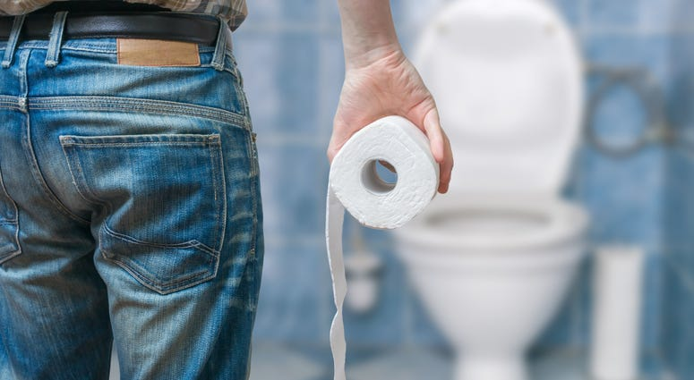 Stock image of a man holding toilet paper in the bathroom