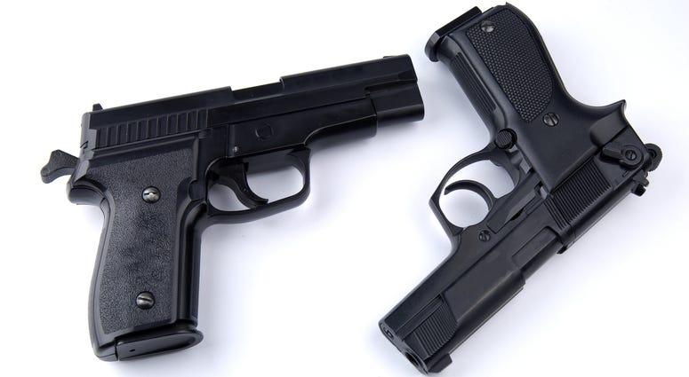 Photo of black guns on the white background