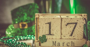 St. Patricks day concept - green beer and symbols, wood calendar, rustic background