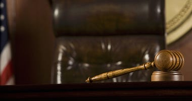 Wooden gavel lying on table by judge's chair in courtroom