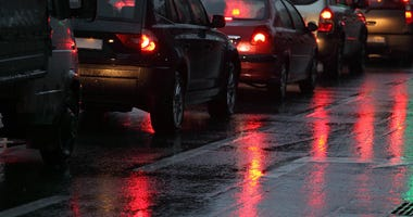 Cars in traffic jam on wet road at rainy city evening