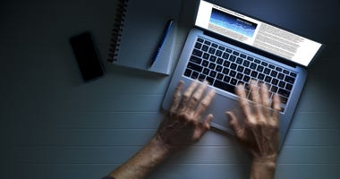 Hands using a laptop computer at night or in the dark, with a business article on the screen