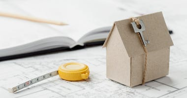 Model of cardboard house with key and tape measure on blueprint. Home building, architectural and construction design concept