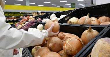 Woman picking fresh onion inside Walmart store