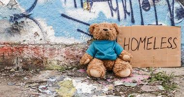 a teddy bear sits next to a cardboard homeless sign