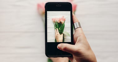 a woman takes a photo of flowers on her smartphone