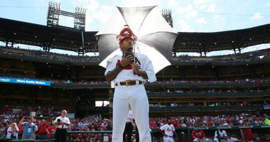 St. Louis Cardinals pitcher Carlos Martinez with an umbrella and catchers mask