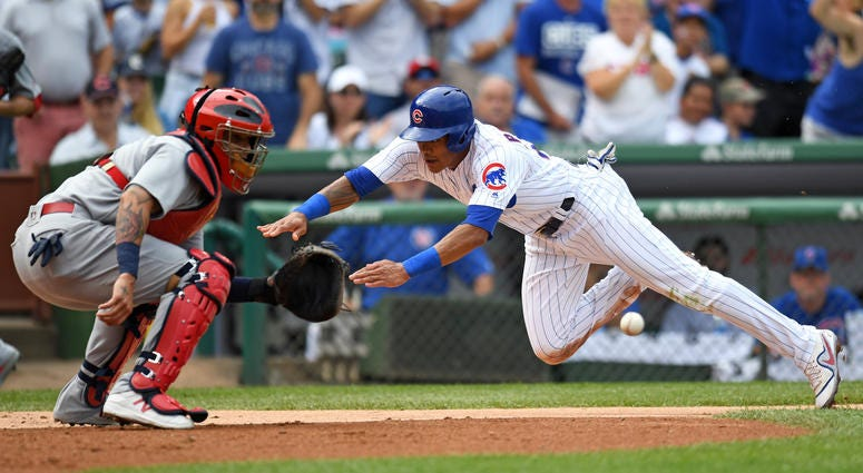 Chicago Cubs shortstop Addison Russell slides safely into home plate against St. Louis Cardinals catcher Yadier Molina