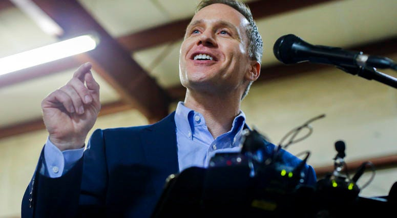 """Missouri Gov. Eric Greitens cheers on a crowd after several protestors were removed from the building before a ceremonial signing making Missouri a """"right-to-work"""" state"""