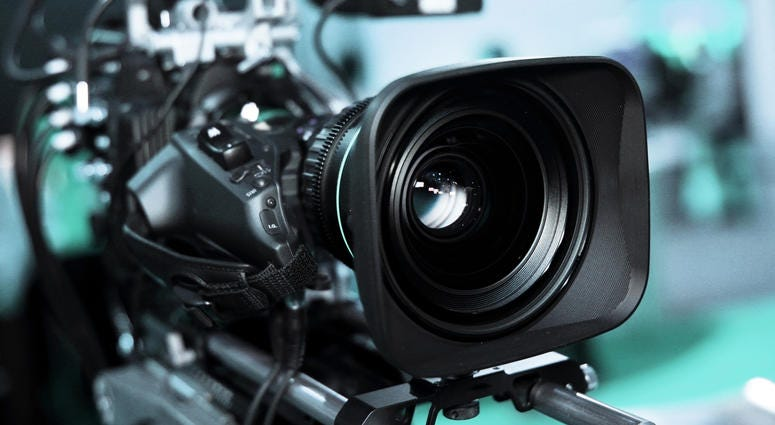 Large professional black video camera filming TV