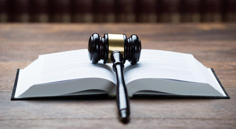 Closeup of mallet on open legal book at table in courtroom