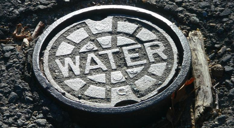 Cast iron water main manhole cover in potholed road