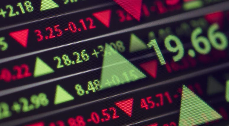 A stock market ticker shows stock gains and losses for the day