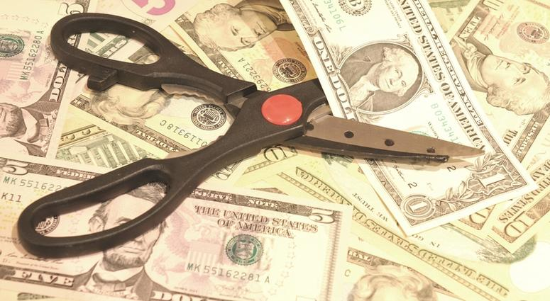 Budget cut concept with scissors and US dollars