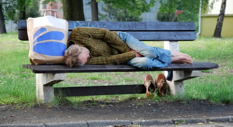 Old homeless man sleeping on bench
