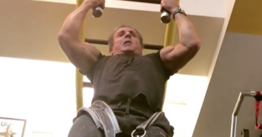 Sylvester Stallone performs a pull up with a 100-pound weight around his waist.
