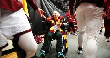 Loyola Ramblers team chaplain, Sister Jean Dolores Schmidt, 98, high fives Loyola players,