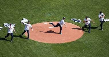 The gold-medal winning USA men's curling team throws out ceremonial first pitches before the Minnesota Twins' home opener .jpg