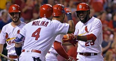 St. Louis Cardinals center fielder Dexter Fowler (25) celebrates with left fielder Tommy Pham (28) and catcher Yadier Molina (4) after hitting a grand slam