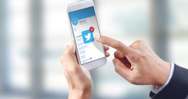Businessman hand touch twitter icon on mobile screen, social media