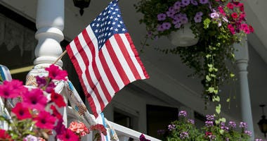 American flag on the railing of a house porch with flower baskets.