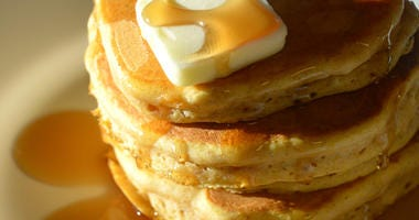 Pumpkin Pancakes with butter and syrup. The dramatic morning light shines in on them.