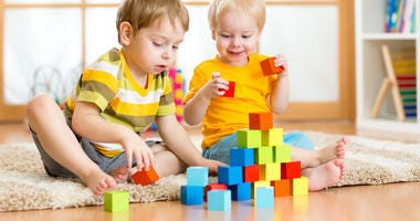 Kids playing block toys in playroom at nursery
