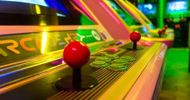 Detail of an arcade game machine with essential components: a joystick and a group of buttons. Classic.