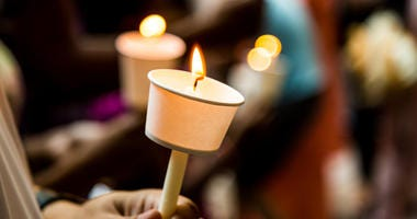 Closeup of people holding candle vigil in dark seeking hope