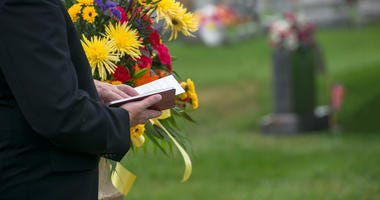 A pastor or minister reads from the Bible during a funeral burial memorial service at a cemetery. Death and grief are a fact of life.