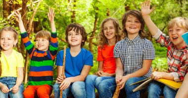 Portrait of happy boy scouts and girl scouts having fun, sitting on the log, in the outdoor summer camp