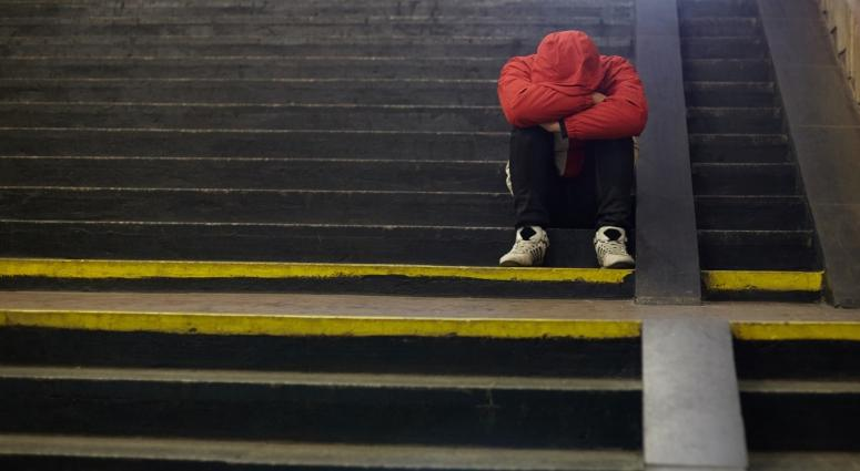 person sitting on stairs with head down