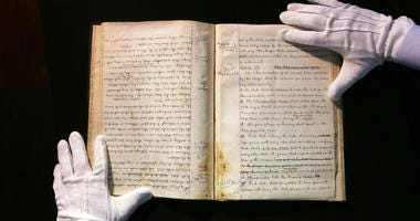 This May 18, 2017, file photo, shows the hands of SCP Auctions vice president Dan Imler holding the 1876 constitution that founded the National League and the modern business of big league sports.