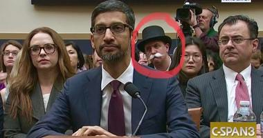 Monopoly man appears in back of congressional hearing.