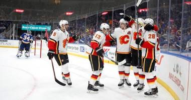 Calgary Flames' Matthew Tkachuk, second from right, is congratulated by teammates after scoring past St. Louis Blues goaltender Jake Allen