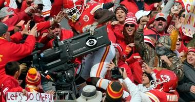 Kansas City Chiefs quarterback Patrick Mahomes (15) watches as wide receiver Tyreek Hill (10) climbs behind a television camera