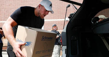 Houston Texans defensive end J.J. Watt places a box of relief supplies in the back of a vehicle to people impacted by Hurricane Harvey, in Houston.
