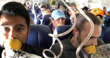 In this April 17, 2018 photo provided by Marty Martinez, Martinez, left, appears with other passengers after a jet engine blew out on the Southwest Airlines Boeing 737 plane he was flying in from New York to Dallas, resulting in the death of a woman who w